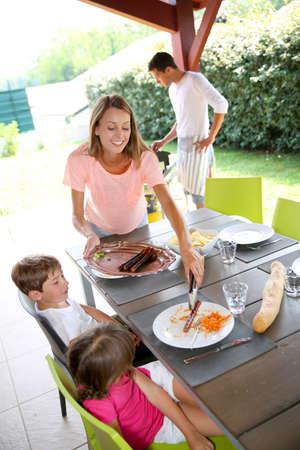 papa y mama: Mam� sirve comida a la parrilla a los ni�os