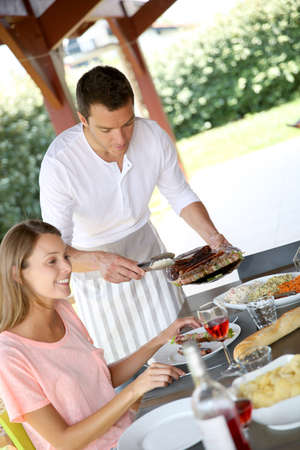 Man serving grilled food to family photo