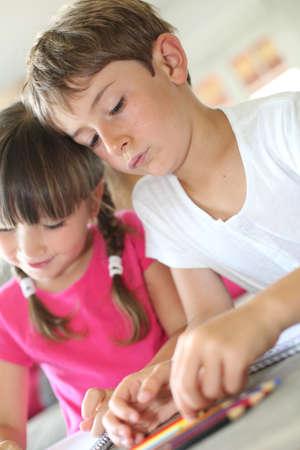 hermanos jugando: Retrato de niños en el hogar dibujo con lápices Foto de archivo