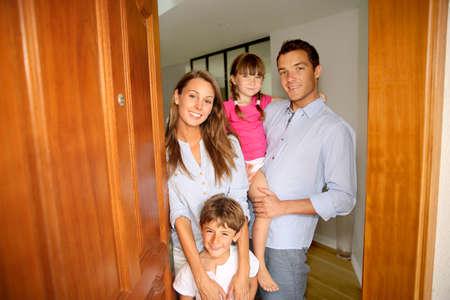 porta aperta: Famiglia in piedi sulla porta d'ingresso della nuova sede Archivio Fotografico