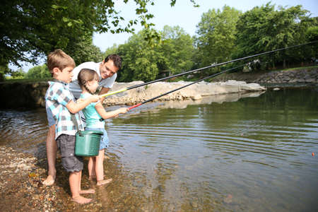 sports fishing: Man teaching kids how to fish in river Stock Photo