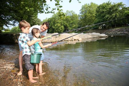 Mens lesgeven aan kinderen hoe om te vissen in de rivier