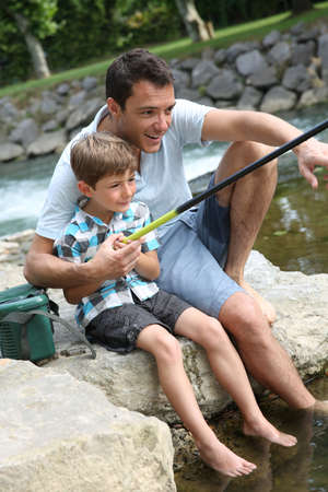 Father teaching son how to fish in river photo