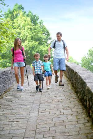 Family on a rambling journey crossing roman bridge photo