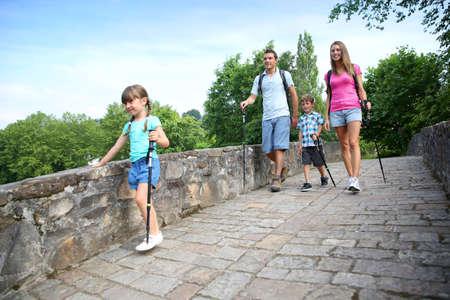 ni�os caminando: Familia en un viaje cruzando el puente romano senderismo Foto de archivo
