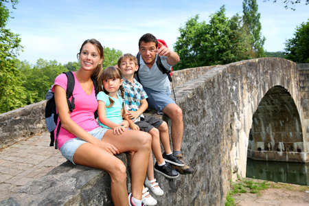 Happy family relaxing on a bridge  photo