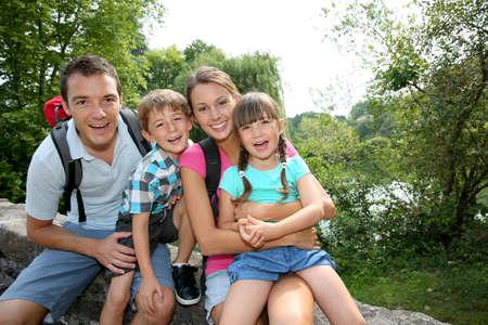 familias felices: Familia feliz que se relaja en un puente Foto de archivo