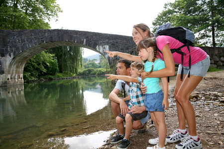 family vacation: Family on a hiking journey standing by the river