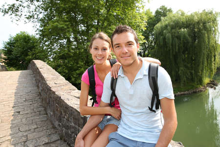 두서없는: Couple on a rambling day sitting on a roman bridge 스톡 사진