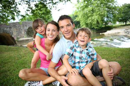 grownups: Family relaxing by river in countryside Stock Photo