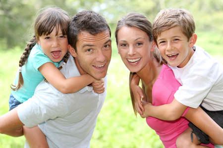 piggyback ride: Portrait of happy parents holding kids on their back Stock Photo