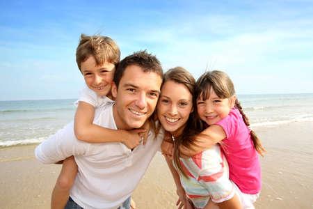 Parents donnant la conduite de ferroutage pour enfants ? la plage Banque d'images - 21090396