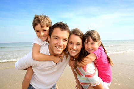 piggyback ride: Parents giving piggyback ride to kids at the beach Stock Photo