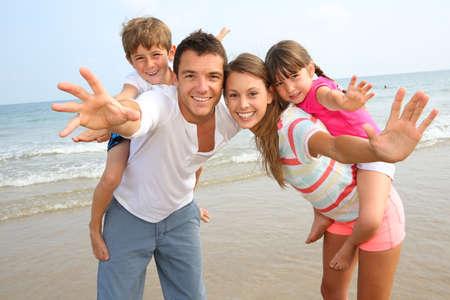 diversion: Los padres que dan a cuestas paseo a los ni?en la playa Foto de archivo