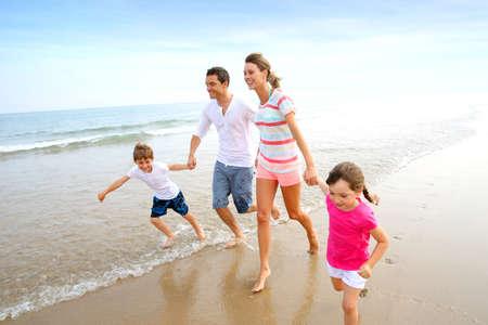 해변에서 실행하는 행복 한 가족