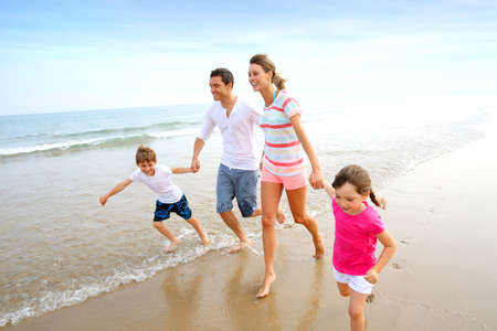Happy family running on the beach photo