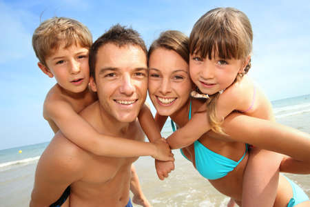 piggyback: Portrait of happy family at the beach