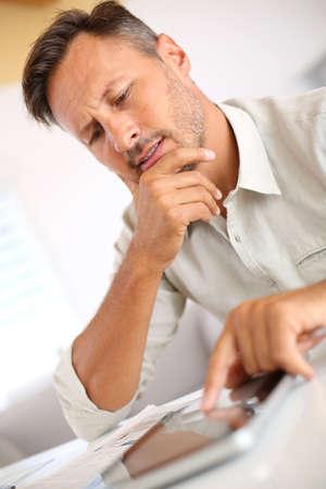 websurfing: Handsome guy websurfing on internet with tablet