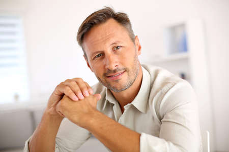 unshaved: Attractive smiling man relaxing at home