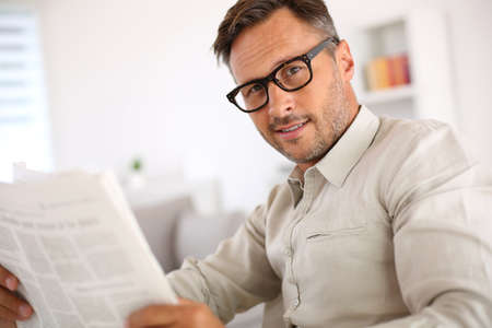 reading glasses: Friendly guy with eyeglasses reading newspaper Stock Photo