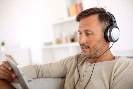 Man relaxing in sofa with tablet and headphones on photo