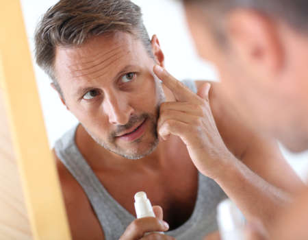 dermatology: Man in bathroom applying cosmetics on his face