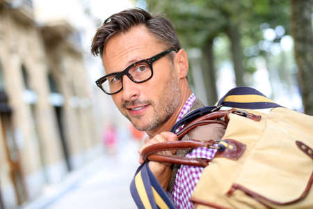 40 years old man: Trendy smiling guy traveling with bag