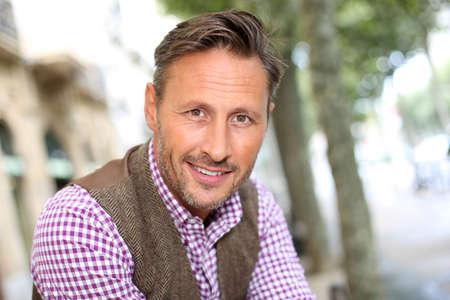 přátelský: Elegantní s úsměvem muž, který stojí v ulici Reklamní fotografie