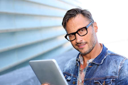 Man with blue jeans jacket using digital tablet Stock Photo - 21979086