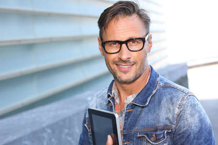 Man with blue jeans jacket using digital tablet photo