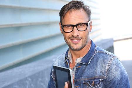 blue jeans: Man with blue jeans jacket using digital tablet