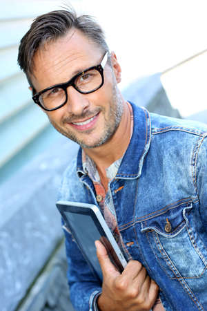 Man with blue jeans jacket using digital tablet Stock Photo - 21979088