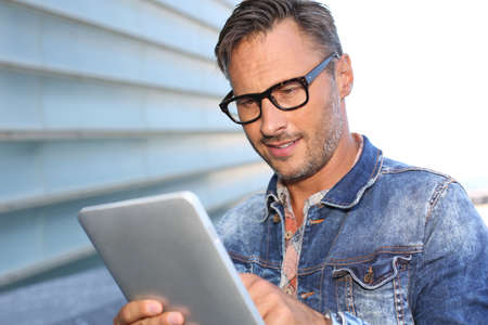 Man with blue jeans jacket using digital tablet Stock Photo - 21979091