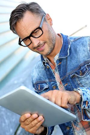 Man with blue jeans jacket using digital tablet Stock Photo - 21979092