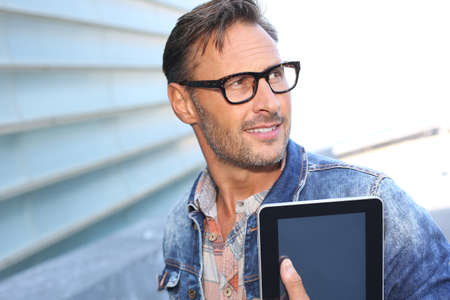 Man with blue jeans jacket using digital tablet Stock Photo - 21979093