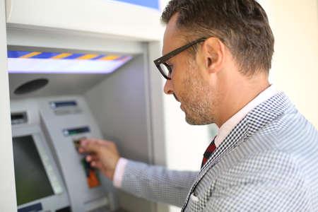 Man die geld van geldautomaat