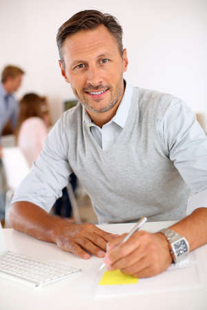ležérní: Veselý muž sedí v kanceláři a pracují na ploše
