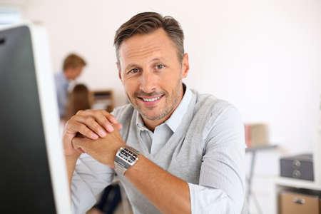 Vrolijke man zit in het kantoor en werken op desktop Stockfoto