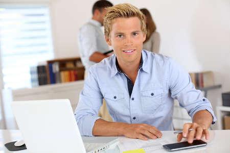 blonde yeux bleus: Portrait de sourire beau jeune homme dans le bureau