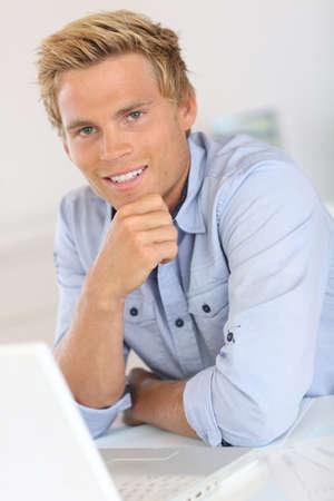 blonde yeux bleus: Vendeur assis devant un ordinateur portable dans le bureau