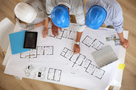 workteam: Upper view of architects working on blueprint
