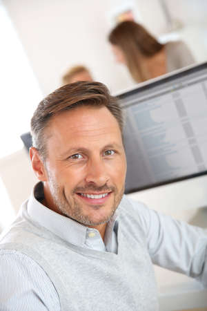 40 years old man: Cheerful man sitting in office and working on desktop