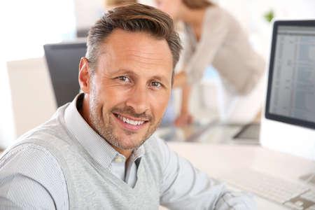 empleado de oficina: Hombre alegre sentado en la oficina y el trabajo en el escritorio Foto de archivo