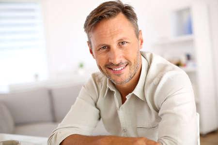 Aantrekkelijke glimlachende man ontspannen thuis