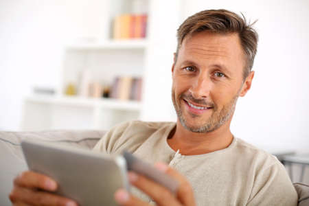 Handsome smiling man at home buying on internet photo