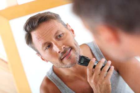Handsome guy shaving in front of mirror photo