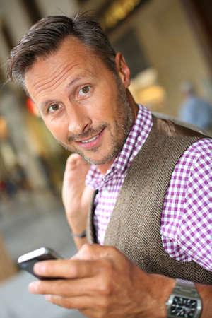 40 years old man: Man in shopping street using mobile phone