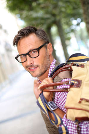 Trendy smiling guy traveling with bag photo