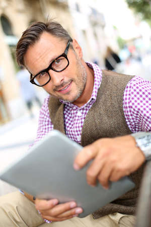 Stylish guy connected on internet with tablet in town photo
