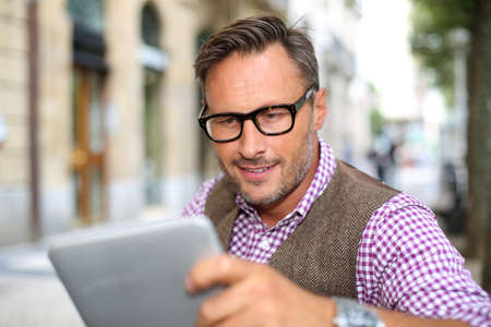 40 years old man: Stylish guy connected on internet with tablet in town